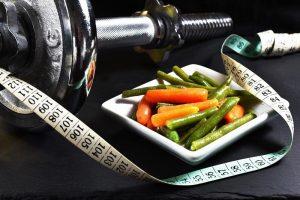 activité physique et santé : photo d'une assiette de légume, d'haltère et d'un mettre ruban